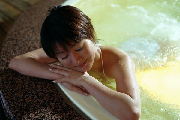 Young woman soaking in hot spring bath, resting chin on hands