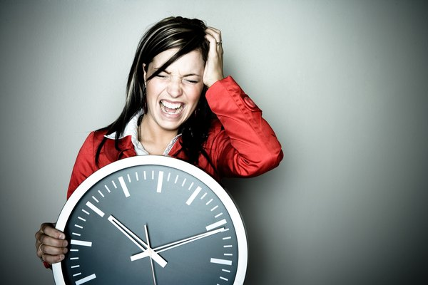 Woman in agony holding wall clock