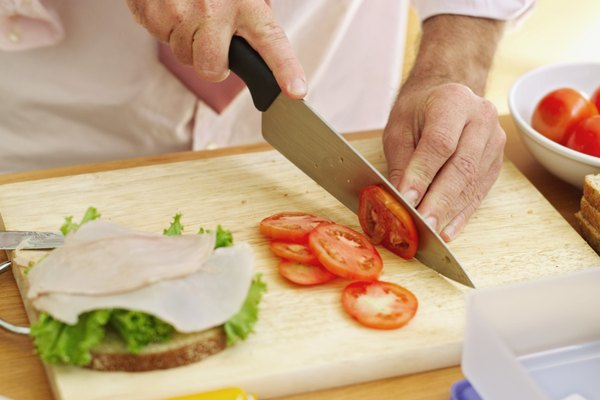 mid section view of a man slicing a tomato on a cutting board