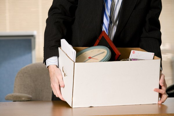 Businessman at desk with box of his belongings