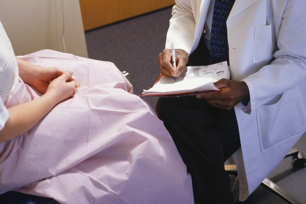 Doctor filling in gynaecological chart, close-up, mid section, elevated view