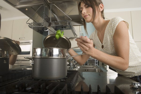 Young woman at stove in kitchen, checking broccoli in saucepan