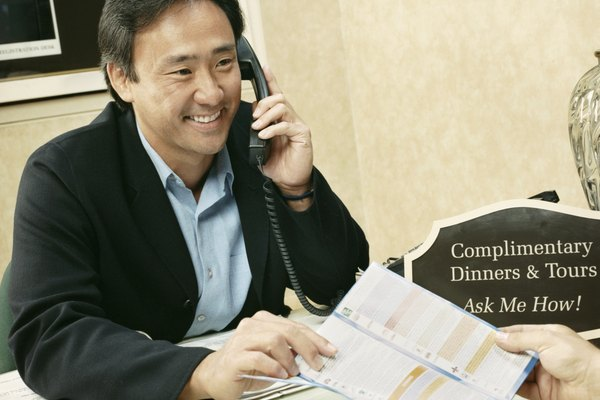 Male Receptionist Sits Behind a Hotel Reception Desk, Talking on the Phone and Handing Over a Brochure
