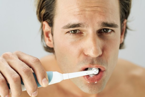 Portrait of a young man brushing teeth with electric toothbrush