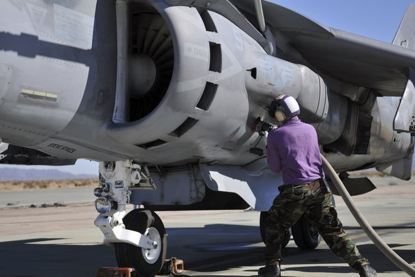 Aviation fuel technician attaches a fuel line to an AV-8B Harrier.