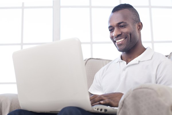 A young man typing on his laptop at home