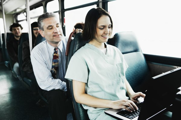 Woman using laptop computer on bus