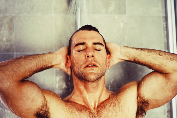 Young man taking a shower with eyes closed