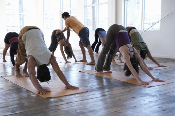 Male yoga instructor teaching class of six adults