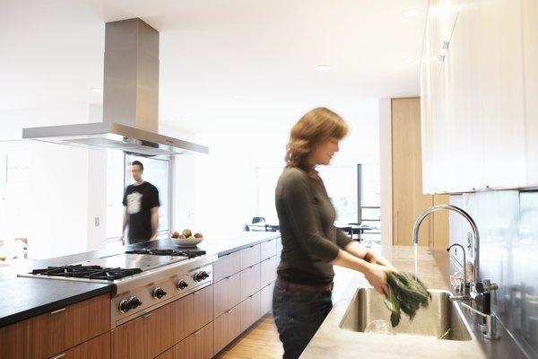 Woman washing lettuce in kitchen sink, man walking past in background