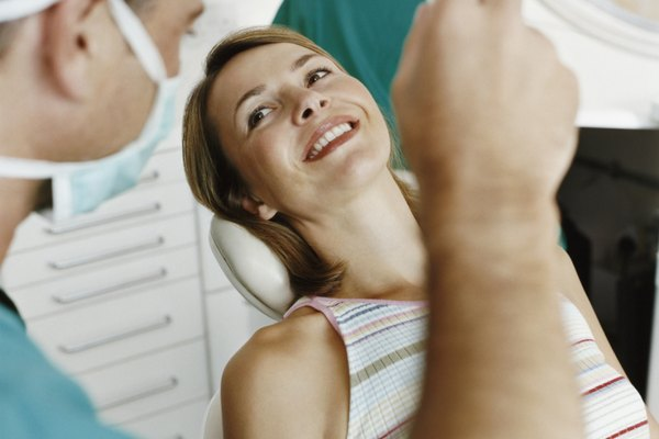 Female Patient Sitting in a Dentist Chair; Dentist Adjusting the Surgical Lamp