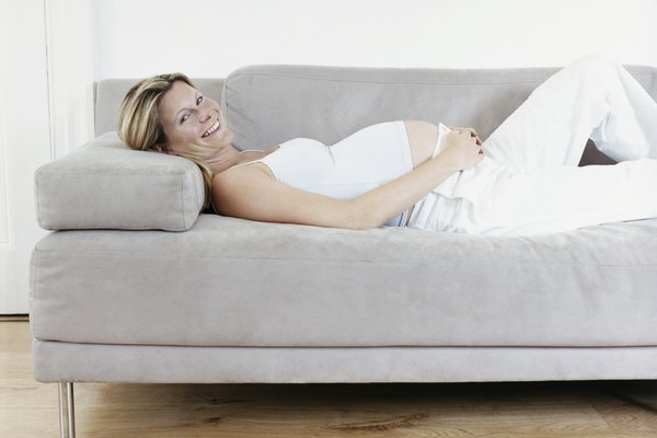Smiling Pregnant Woman Lying on Sofa