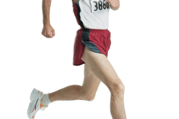 a caucasian man with a mustache is wearing a red track uniform and a marathon number as he runs
