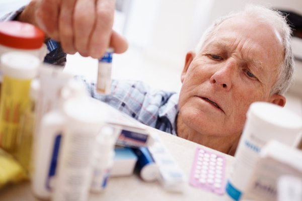 Elderly man picking medicine bottle from a shelf