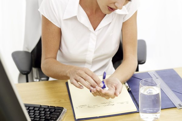 high angle view of a businesswoman taking tablets sitting at her desk