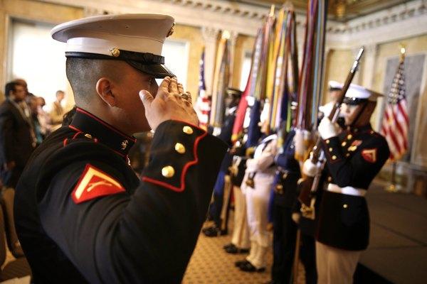Un Marine saludando a un equipo de la guardia de honor.