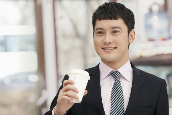 Smiling business man holding coffee cup