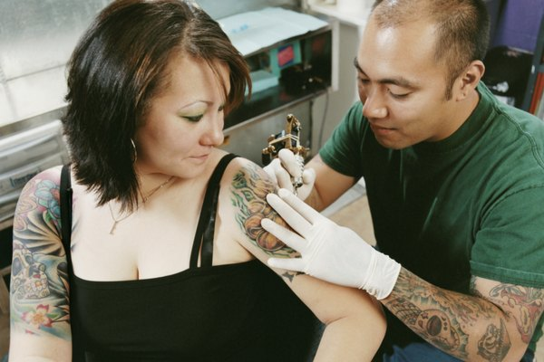 Tattooist Tattooing a Woman's Arm