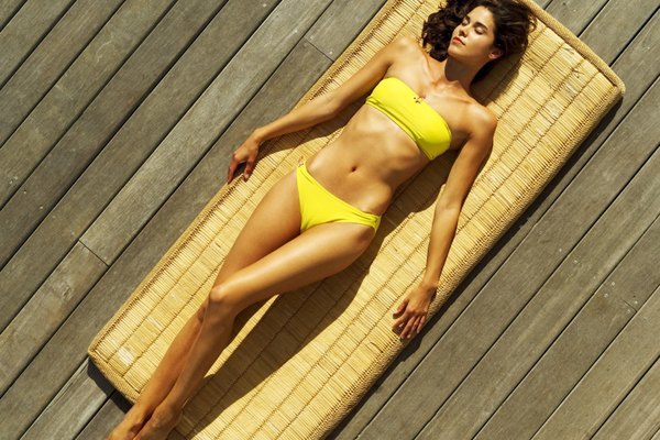 Elevated view of a woman wearing a bikini lying on a straw mat