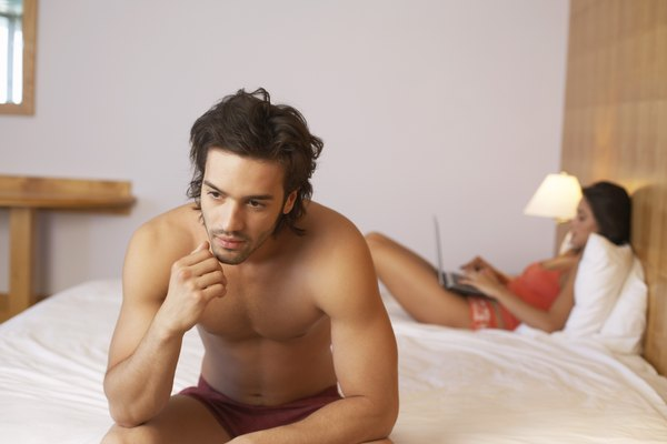 Unhappy man sitting on edge of bed