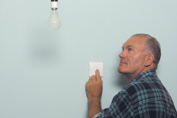 Man turning on light switch