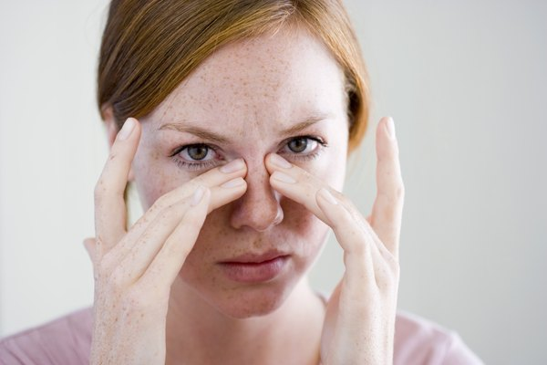 Woman with fingers on nose