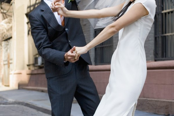 Bride and groom dancing on cobblestone street, New York City, NY