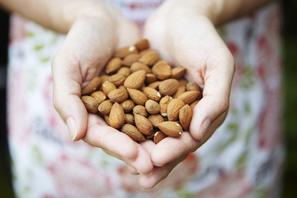 Woman Holding Handful Of Almonds