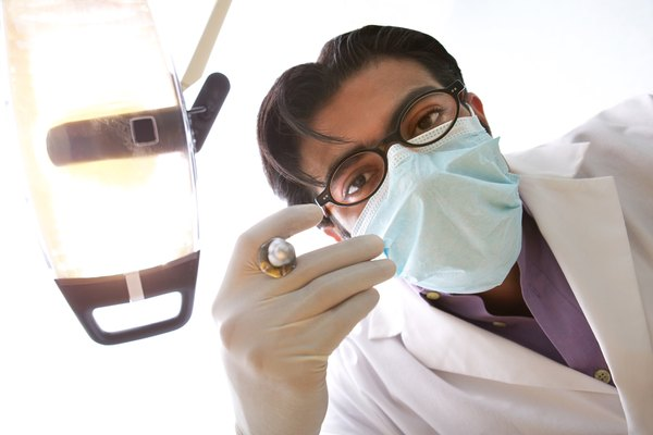 Point of view of a dentist holding a syringe with Novocaine in it over the patient's mouth