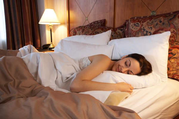 Woman sleeping in hotel bed