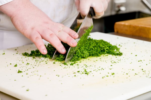 Close-up of chef chopping parsley