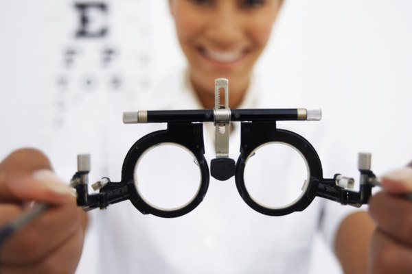 Close-up of eye testing spectacles in a young female optometrists hands (blurred)