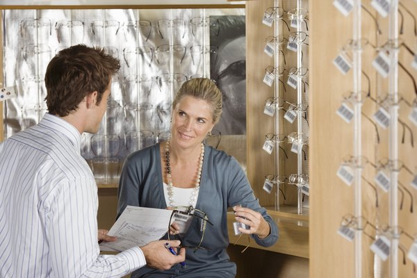 Salesman assisting woman in eyeglasses store