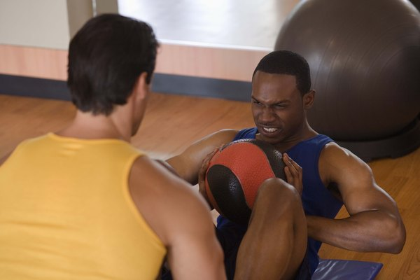 Personal trainer holding feet of man doing sit-ups