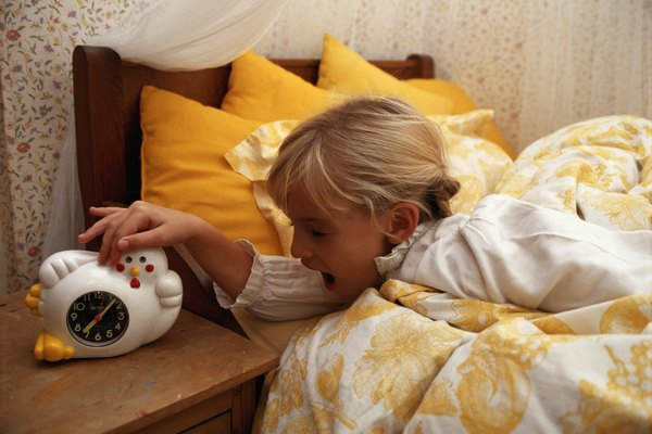 Girl (4-5) on bed turning off alarm clock