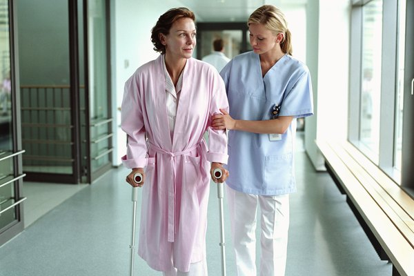 Female nurse holding patient using crutches in hospital corridor