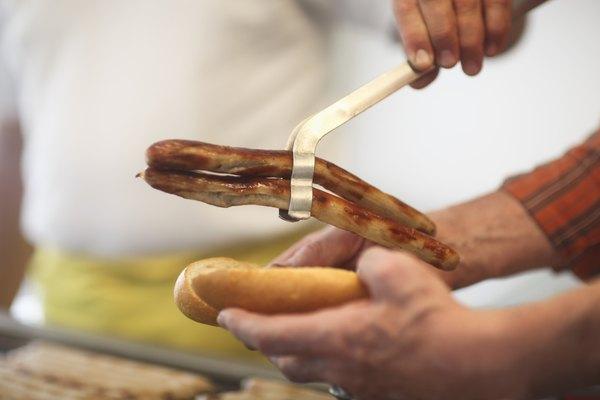 Man serving sausages at market, close up