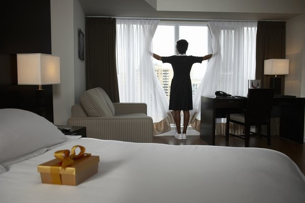 Chambermaid opening curtains, box of chocolates on guest's bed