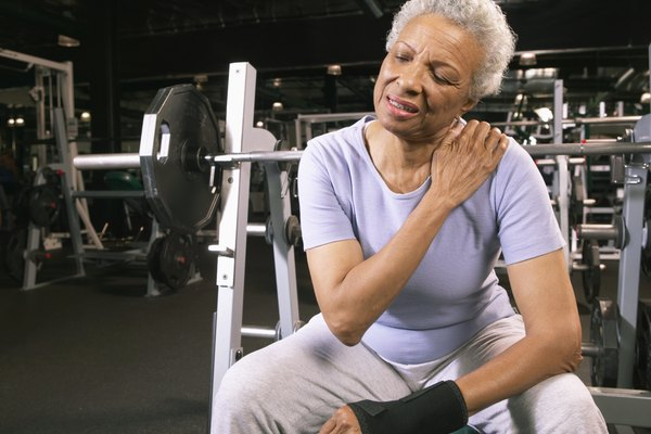 Senior woman in gym wearing wrist strap, rubbing shoulder