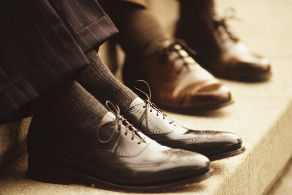 Two businessmen sitting on steps, Close-up of feet