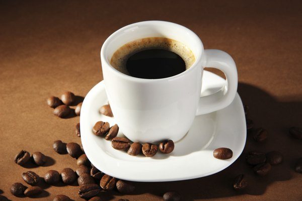 Cup of coffee with  beans on brown background
