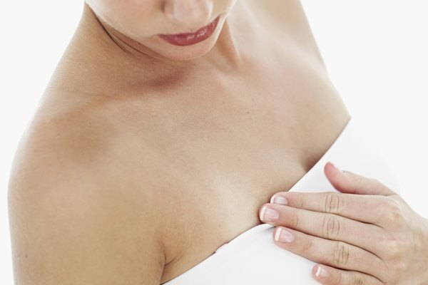 Close-up of a young woman touching and looking at her breast