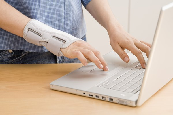 Hands in wrist brace using laptop