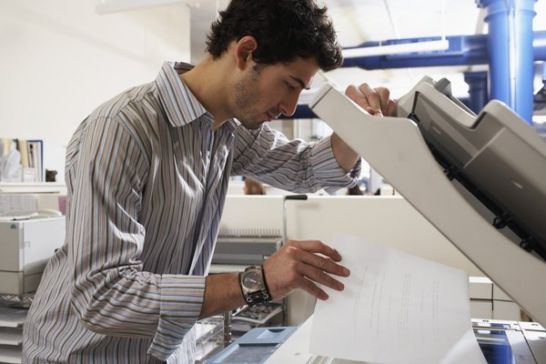 Male office worker using photocopier, placing paper scanning area