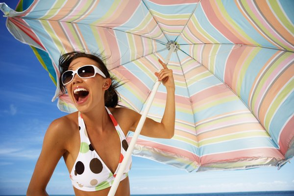Young woman holding beach umbrella, laughing, close-up