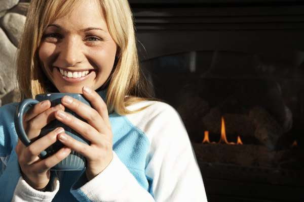 Woman holding coffee cup beside fireplace, smiling, portrait