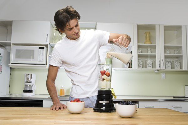 Young man in kitchen, pouring milk into blender