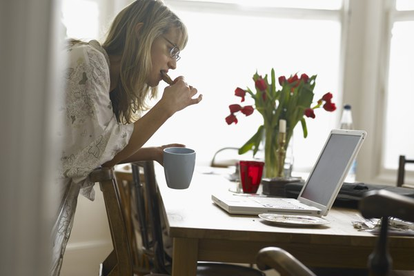 Woman eating breakfast while looking at laptop