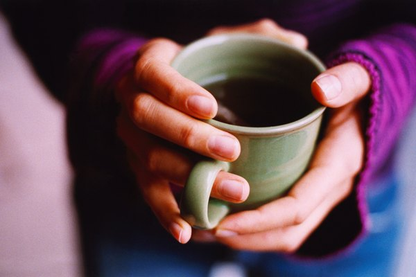 high angle view of hands holding a cup of coffee