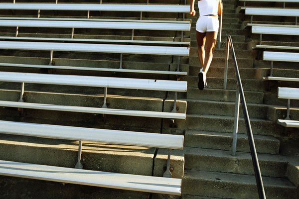 Woman running stairs of stadium, rear view